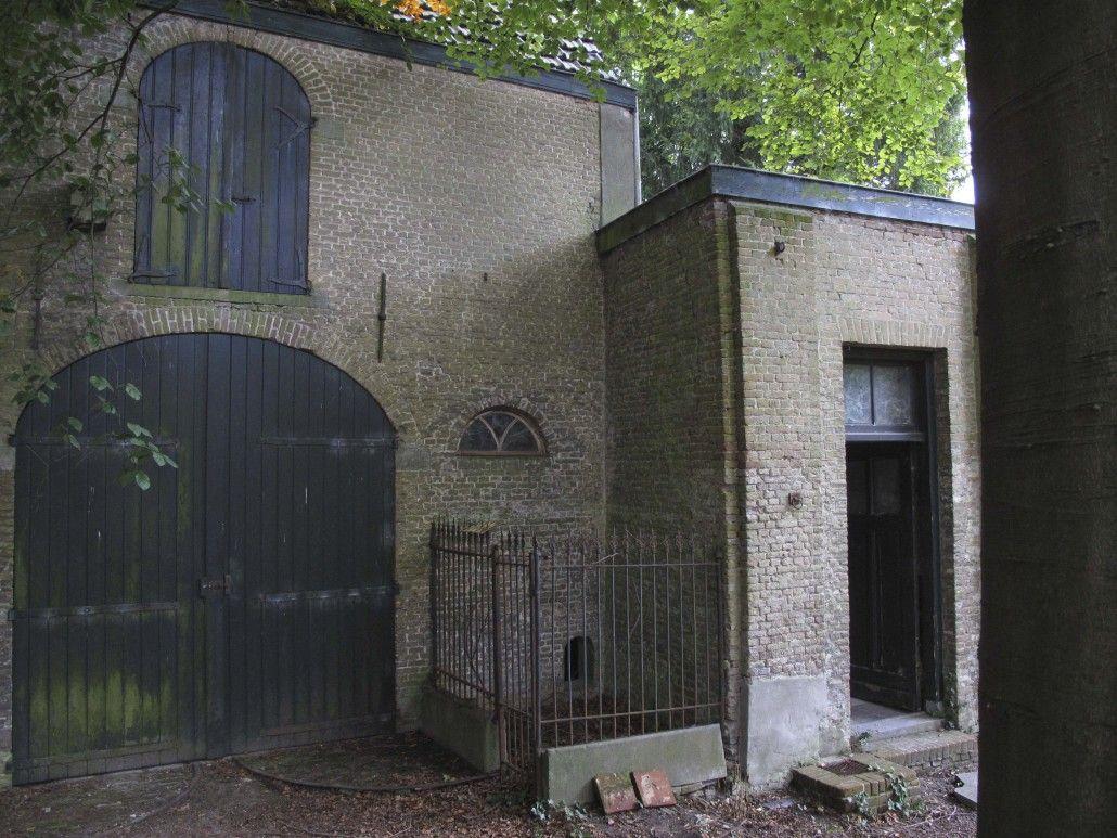 Het koetshuis links met rechts de deur van de koetsierswoning in het stalgebouw.